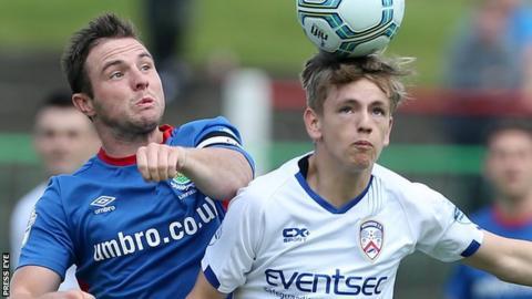 Linfield captain Jamie Mulgrew closes in on Ciaron Harkin in Saturday's win over the Bannsiders