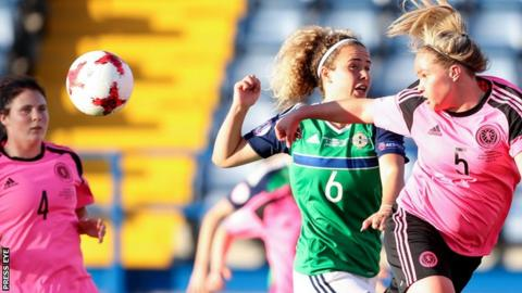 Courtney Whyte heads clear for Scotland as Brenna McPartlan closes in during the Group A encounter