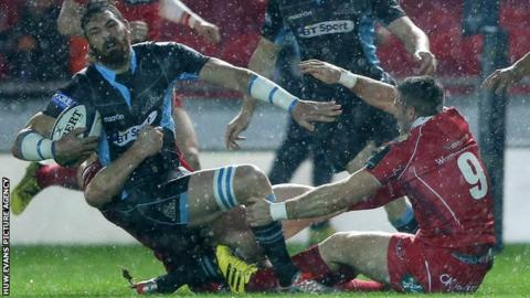 Glasgow winger Sean Lamont is tackled by Scarlets pair Jack Condy and Gareth Davies