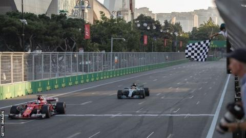 Sebastian Vettel crosses the line at the Azerbaijan Grand Prix before Lewis Hamilton