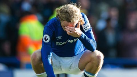 Tom Davies is dejected after Everton's defeat by Arsenal