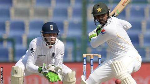 Jos Buttler stands at the wicket while Shoaib Malik hits out for Pakistan