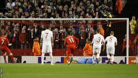 Liverpool midfielder James Milner (centre) scores a penalty against Augsburg