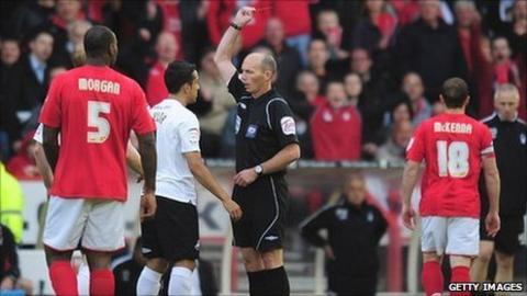 Referee Mike Dean sends off Swansea defender Neil Taylor at Nottingham Forest