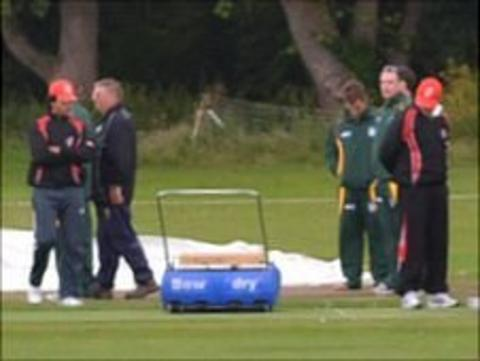 Guernsey cricket players and umpires inspecting KGV under rainy conditions
