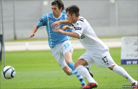 Mark Surgenor of Ballymena United competes for possession with Lisburn Distllery's Jordan Hughes