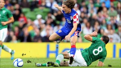 Luka Modric is tackled by Darron Gibson in the Dublin friendly