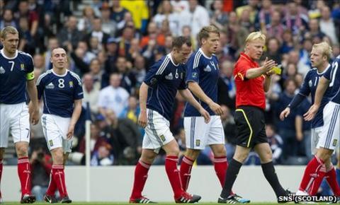 Scotland players surround referee Kevin Blom at Hampden