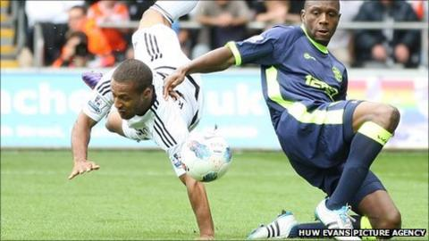 Wayne Routledge takes a tumble against Wigan Athletic