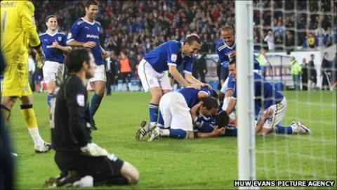 Cardiff players mob Paul Quinn after his penalty shoot-out winner against Leicester