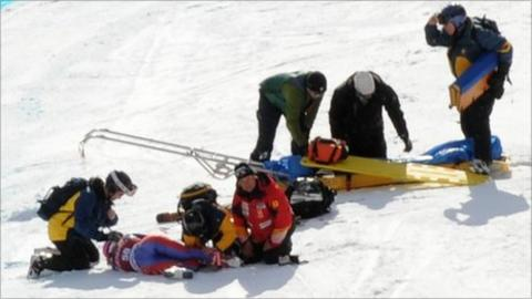 Alcott is treated on the piste after breaking her leg in Canada