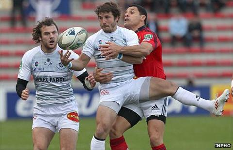 Marc Andreu of Castres is tackled by Munster's Dougie Howlett