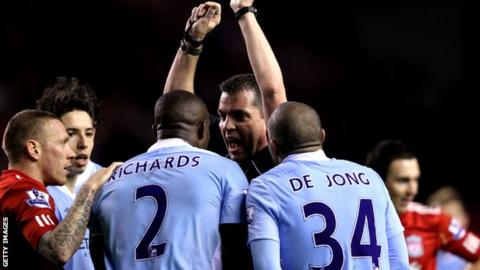 Micah Richards remonstrates with referee Phil Dowd at Anfield