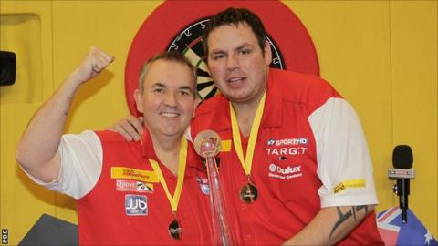 England's Phil Taylor and Adrian Lewis with the World Cup of Darts trophy