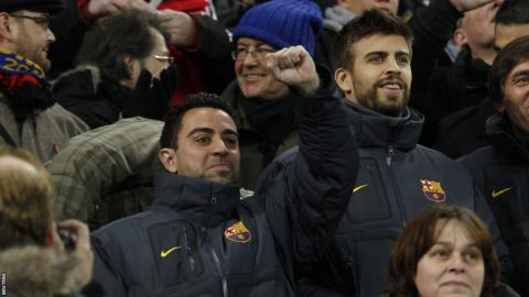Barcelona's Xavi and Gerard Pique