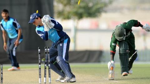Scotland wicket keeper Craig Wallace breaks the stumps to run out Shem Ngoche