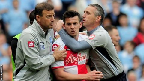 QPR midfielder Joey Barton is restrained following his red card