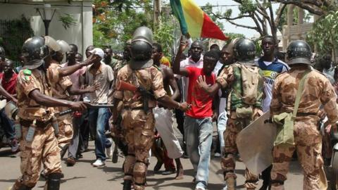 Malian riot police try to prevent demonstrators entering the presidential compound on 21 May