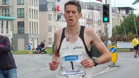 Lee Merrien crosses the line at the Guernsey half marathon