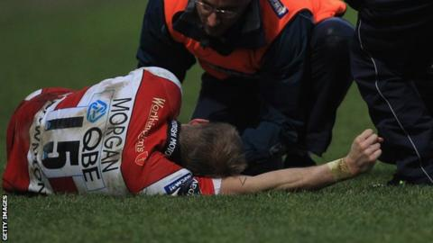 Olly Morgan receives medical attention in the game against Worcester Warriors