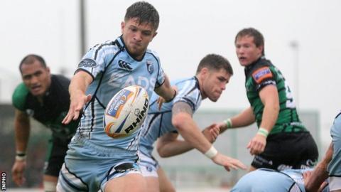 Cardiff's Lewis Jones kicks the ball clear