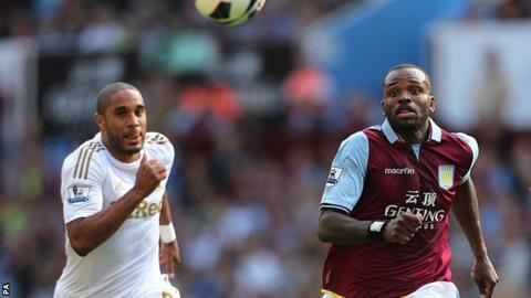 Swansea defender Ashley Williams challenges Darren Bent of Aston Villa