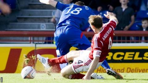 Shane Sutherland is tackled by Russell Anderson at Caledonian Stadium