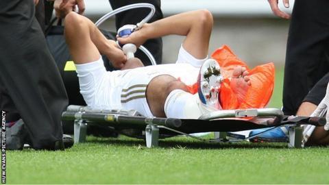 Neil Taylor lies injured on a stretcher