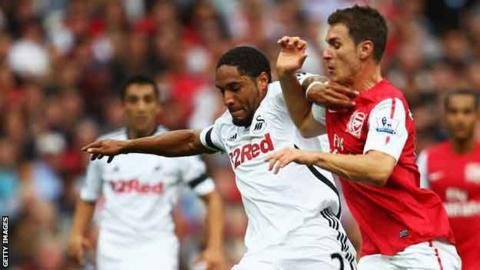 Ashley Williams and Aaron Ramsey compete for their clubs