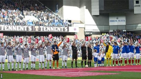 Queen's Park and Rangers players prepare for kick-off in front of a large crowd at Ibrox