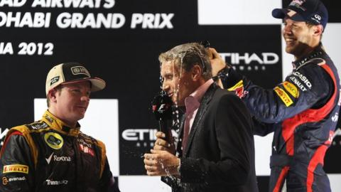 David Coulthard is drenched by Sebastian Vettel while interviewing Kimi Raikkonen (left).