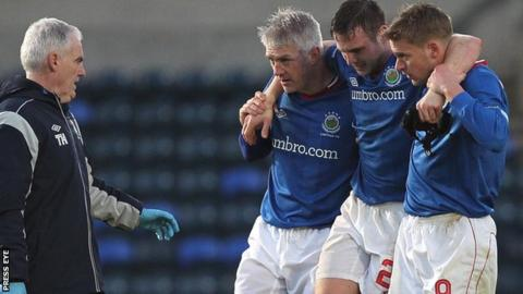 Linfield's Jamie Mulgrew is helped off the pitch by team-mates William Murphy and Peter Thompson