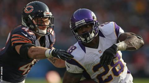 Adrian Peterson (right) powers past a member of the Chicago Bears defence