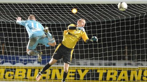 Ballymena United forward David Cushley sends his effort on goal but Lisburn Distillery keeper Billy Brennan gets across to make the save