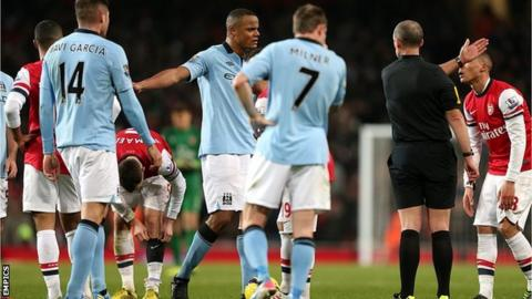 Manchester City captain Vincent Kompany (right) is sent off by referee Mike Dean