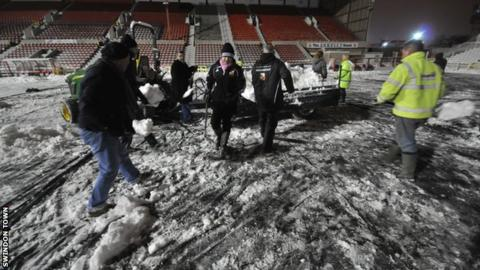Volunteers help clear the snow at Swindon Town's County Ground