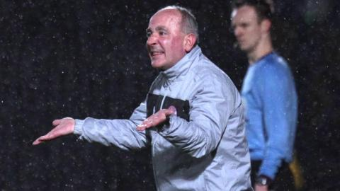 Cliftonville boss Tommy Breslin gives instructions in the Windsor Park rain