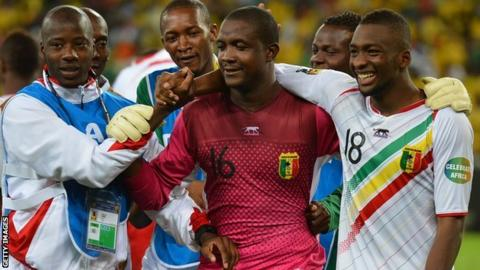 Mali's goalkeeper Soumbeyla Diakite (C) is congratulated by teammates after they beat South Africa on penalties