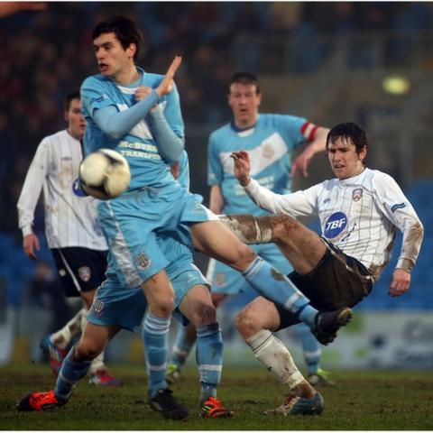 Ballymena United's Mark Surgenor attempts to block the clearance of Coleraine opponent Howard Beverland