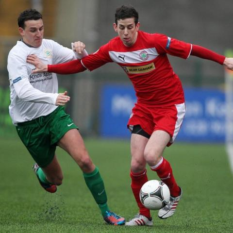 Stephen O'Neill of Donegal Celtic challenges Cliftonville opponent Eamonn Seydak during the Irish Cup tie at Solitude