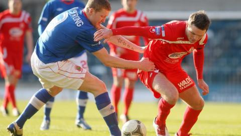 Linfield defender David Armstrong gets to grips with Portadown opponent Kevin Braniff at Windsor Park