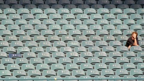 Football fan sitting alone in the stands