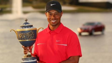 Tiger Woods poses with his trophy