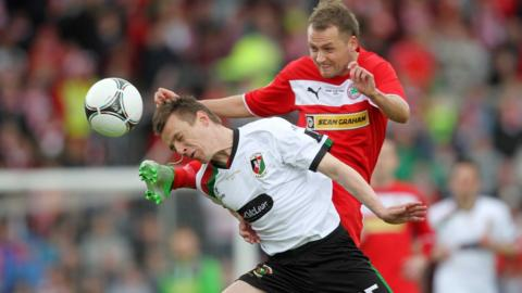 Glentoran defender Jason Hill bravely heads clear to deny Cliftonville's Ciaran Caldwell in Saturday's decider