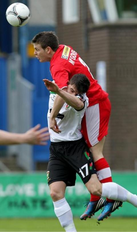 Cliftonville defender Jaimie McGovern gets above Jimmy Callacher to head the ball