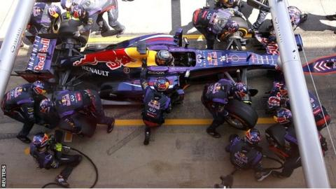 Red Bull staff work on Sebastian Vettel's car at a pit stop in the Spanish Grand Prix