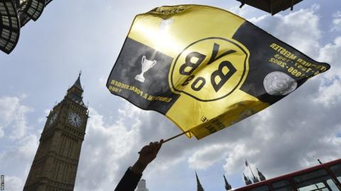 A Borussia Dortmund flag is waved in front of Big Ben