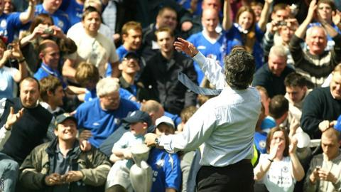 Jose Mourinho throws his winner's medal into the crowd