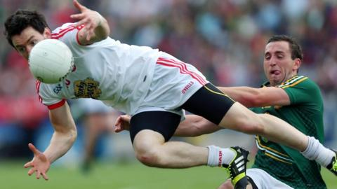 Tyrone's Mattie Donnelly takes a tumble after this challenge from Meath opponent Graham Reilly