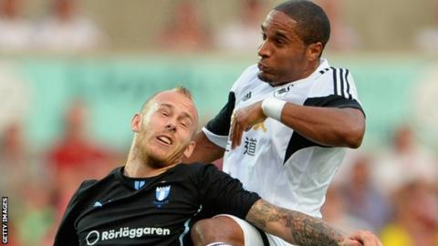 Malmo's Magnus Eriksson challenges Ashley Williams